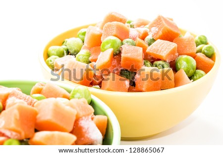 Close-up of a frozen vegetables mix in colorful kitchen bowls isolated on white