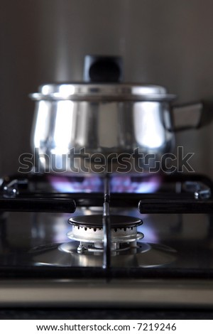 Close up of a gas hob with a pan on the back burner, shallow DOF. - stock photo