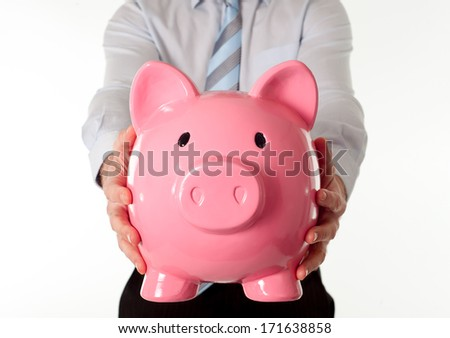 close-up of a giant pink piggy bank with a business man wear a blue shirt and blue tie in the background on a white background