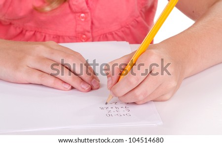 Close-up of a girl doing math problems on white paper - stock photo