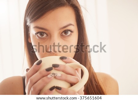 Close up of a girl drinking from a cup. - stock photo