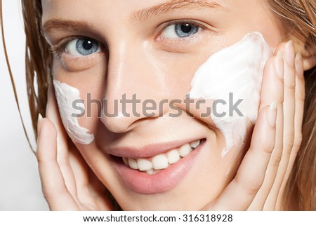 Close-up of a girl put the cream on the skin - stock photo