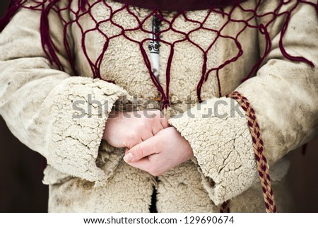 Close up of a girl's hands dressed in traditional Romanian wear - stock photo