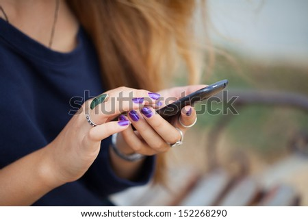 Close up of a girl using mobile smart phone - stock photo
