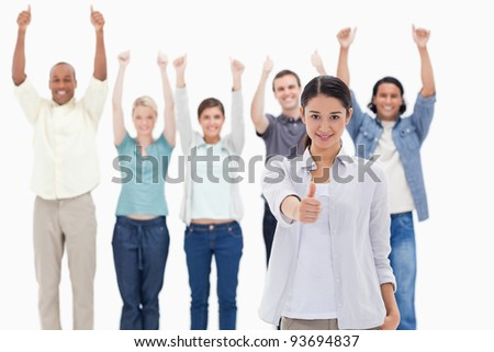 Close-up of a girl with people raising their arms and with their thumbs up in background - stock photo