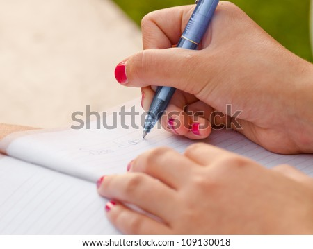 Close-up of a girl writing into her diary, hands - stock photo