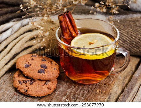 close up of a glass mug of hot drink with a lemon and cinnamon - stock photo