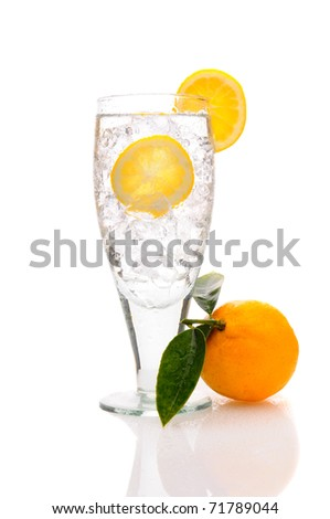 Close up of a glass of sparkling water with ice cubes and lemon. Vertical Format isolated on white with reflection. - stock photo