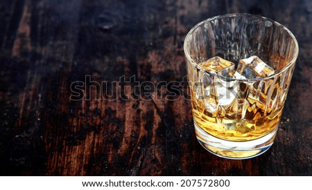 Close-up of a glass of whiskey, bourbon or scotch, with ice cubes, on an old rustic wooden table - stock photo