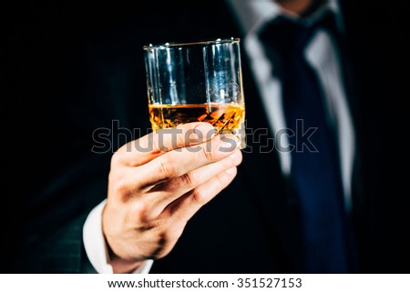 Close-up of a glass of whiskey held by a man in suit