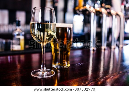 Close up of a glass of wine and a beer in a bar - stock photo
