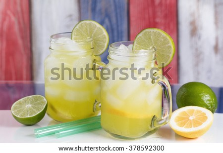 Close up of a glasses filled with cold lemonade.  Faded wooden boards painted red, white and blue in background. Selective focus on upper front jar glass.