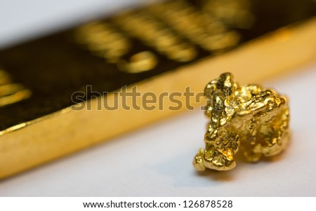 Close-up of a gold-bar and gold-nugget - stock photo