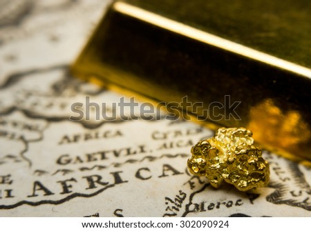 Close-up of a gold-bar and nugget and an old map of Africa - stock photo