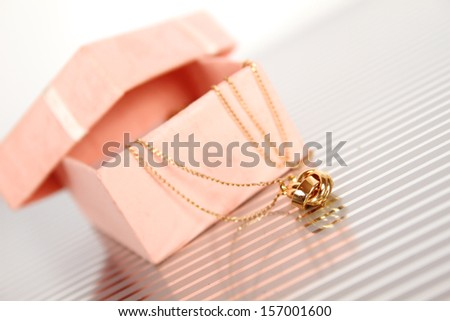Close-up of a gold chain with a pendant in a gift box - stock photo