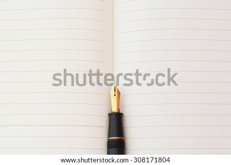 Close,up,of,a,Gold,Fountain,Pen,Nib?and line book - stock photo