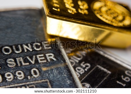 Close-up of a gold-ingot on top of a troy ounce silver and palladium bar - stock photo