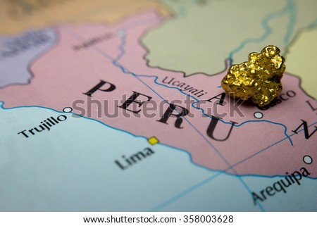 Close-up of a gold nugget on top of a  map of Peru - stock photo