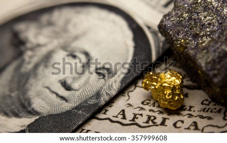 Close-up of a gold nugget / rare earth metal and a 1 dollar note (showing George Washington) on top of an antique map of Africa - stock photo