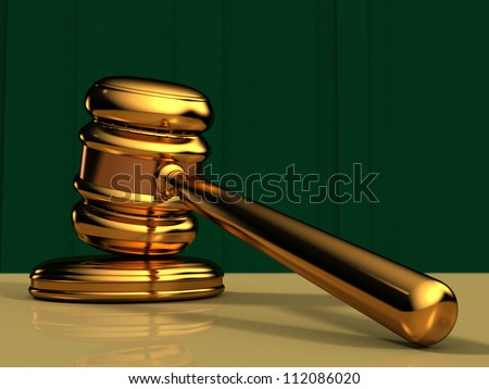 Close Up of a Golden Gavel on a table top with a green curtain background - stock photo