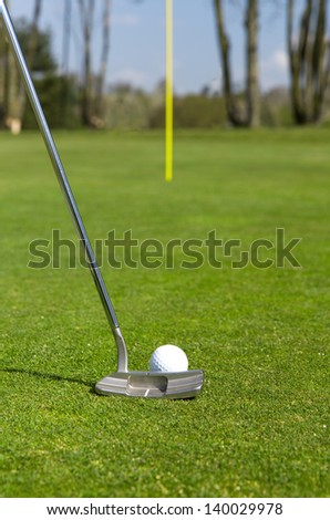 Close up of a golf ball and a putter on a green with a flag in the distance