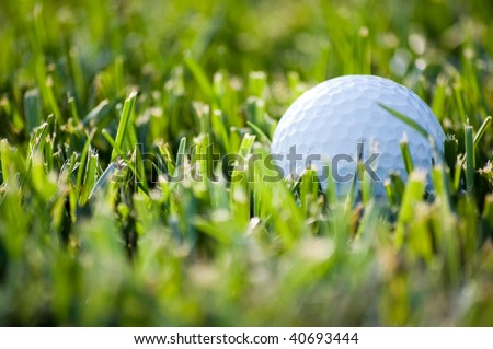 Close-up of a golf ball lying in green grass - stock photo