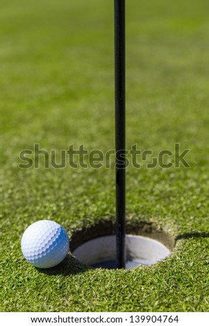 Close up of a golf ball on the edge of a hole. - stock photo
