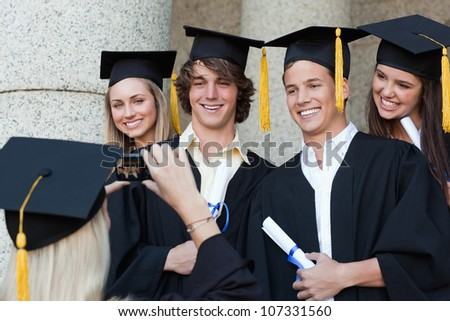 Close-up of a graduate taking a picture of her friend in front of the university - stock photo