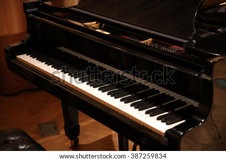 Close up of a grand piano with black and white piano keys - stock photo