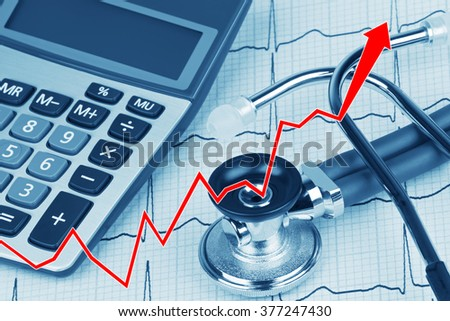 Close up of a graph with an Electrocardiograph also known as a EKG or ECG graph with a stethoscope and calculator showing the high cost of health care - stock photo
