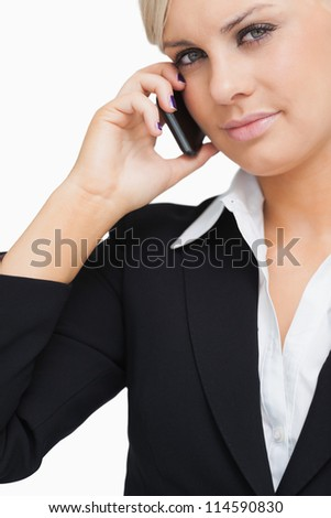 Close-up of a green eyed businesswoman using her mobile against white background