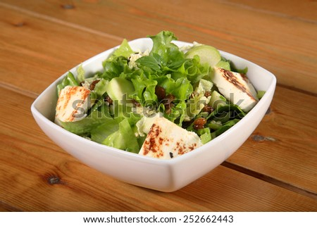 close up of a green salad with cheese and green apple