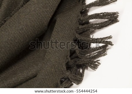 Close up of a green wool scarf with tassels on white background