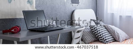 Close-up of a grey desk and bed in a contemporary bedroom