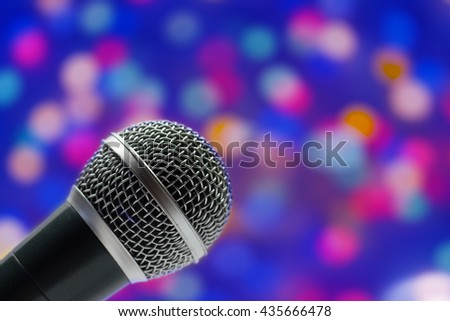 Close-up of a grey microphone in concert hall on abstract blurred background - stock photo