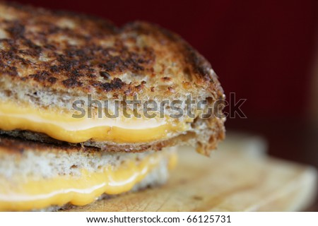 Close up of a grilled cheese with melted cheese in a wood plate - stock photo