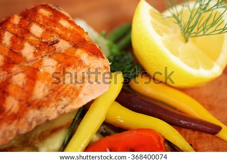 Close up of a grilled salmon decorated on a wooden board