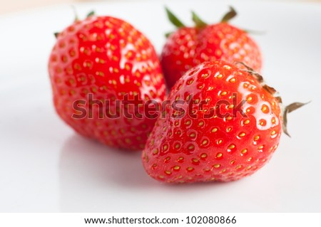 Close up of a group of three fresh strawberries on a white plate, reflection visible.