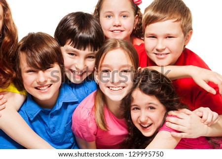 Close-up of a group of 10 years old kids, boys and girls, hugging, smiling, laughing, on white