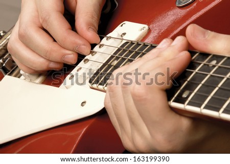 Close-up of a guitar and playing hands, isolated on grey - stock photo