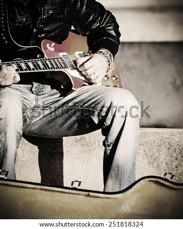 close up of a guitarist playing in the street in vintage effect - stock photo