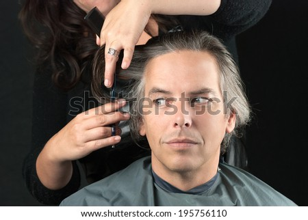 Close-up of a hair stylist removing bulk length. - stock photo
