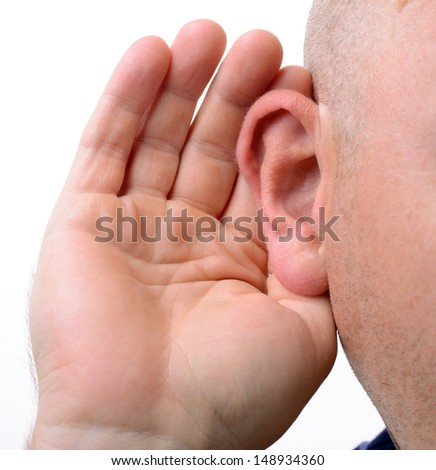 close up of a hand cupping an ear to hear better isolated on white - stock photo