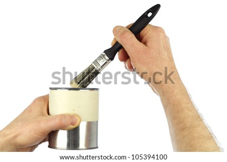 Close up of a hand dipping a small paint brush in a small can of touch up paint being held by the other hand. - stock photo