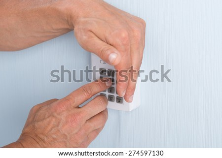 Close-up Of A Hand Entering Pin In Security System - stock photo