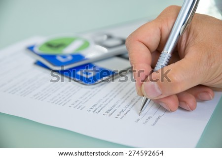 Close-up Of A Hand Filling Car Sale Contract Form With Vehicle Registration Plate On Desk. Contract Paper Contains Placeholder Text - stock photo