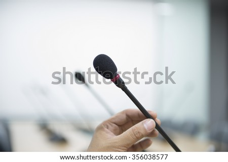 Close up of a hand holding a business conference microphone in a meeting room