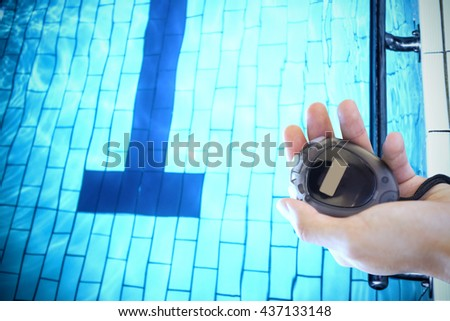 Close up of a hand holding a chronometer close to the swimming pool - stock photo
