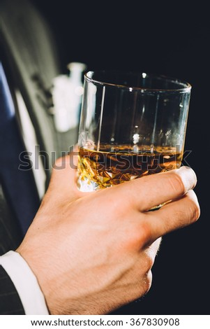 Close-up of a hand holding a glass of whiskey - stock photo