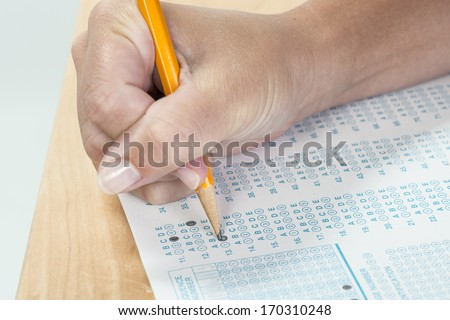 Close up of a hand holding a pencil taking a standardized test - stock photo